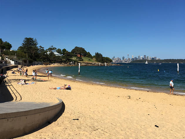 Camp cove beach looking out onto Sydney Harbour with the city skyline in the background