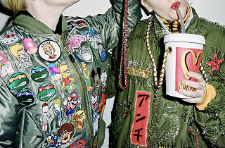 Two people in camo jackets, covered in patches pose with their torsos in view. One drinks from a Moschino big gulp cup.