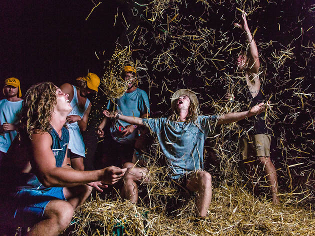 Young men throwing hay and dancing at Mountain Sounds