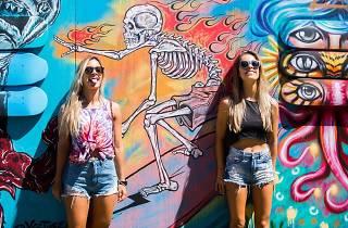 Two women standing next to a graffiti wall