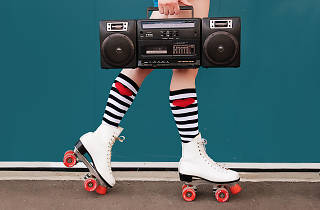 Legs of woman wearing white roller skates with red wheels, holding radio