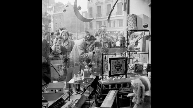 Children peer into Hamleys toy store window, 1957