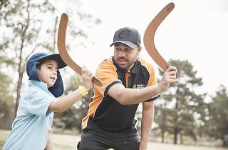 Child and instructor learning how to throw a boomerang