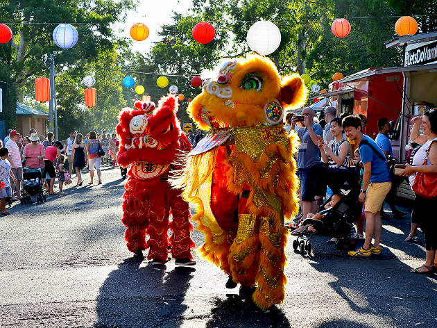 Two people in dragon costumes walking down a street with onlookers and food trucks