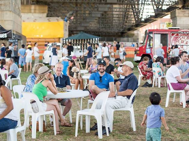 Eventgoers sitting on plastic white chairs at Bradfield Park with the Harbour Bridge in the background