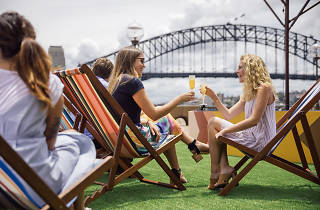 Two women with drinks looking at Sydney Harbour Bridge