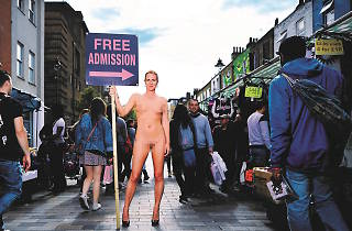 Photo of Ursula Martinez standing naked in a marketplace