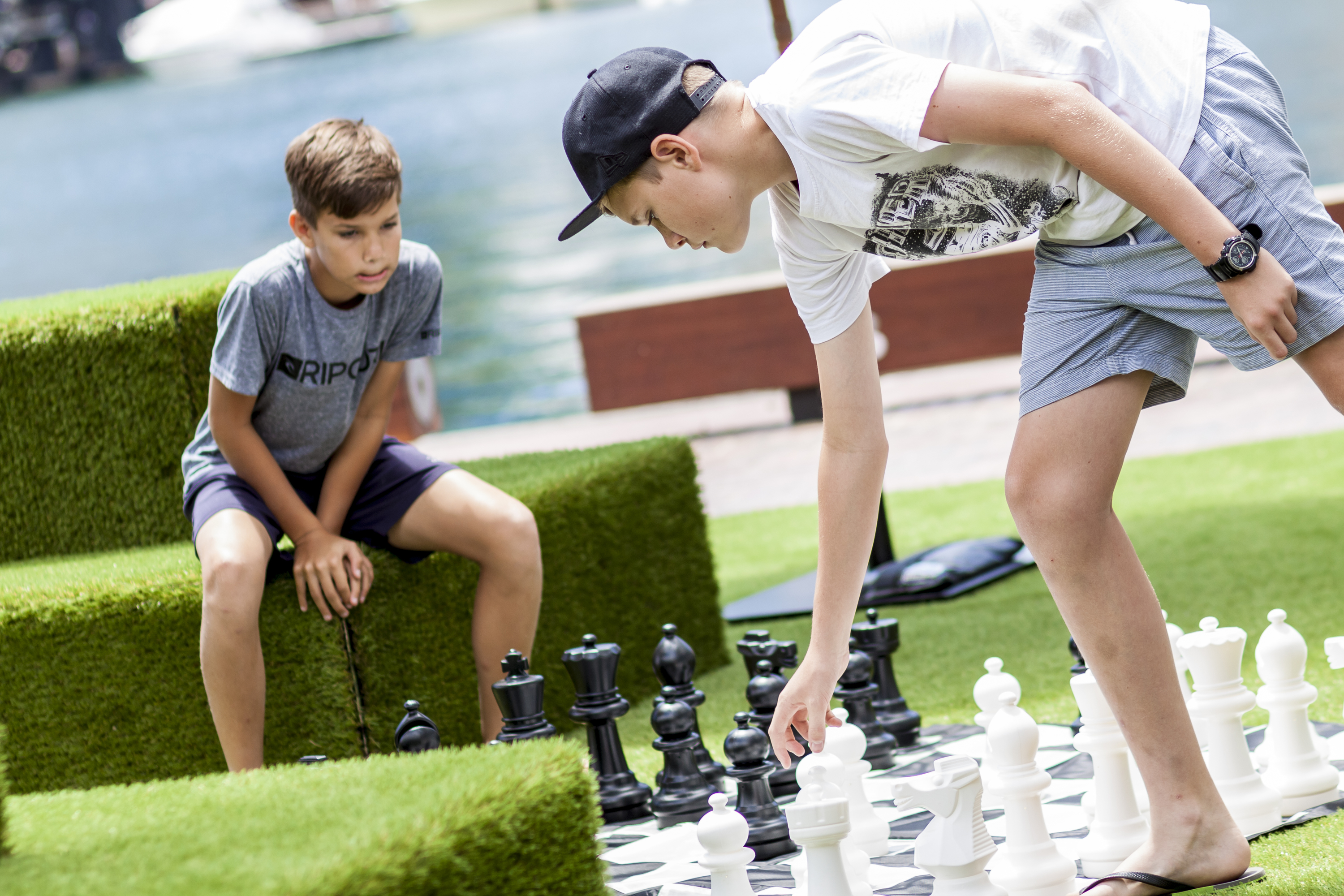 Two boys playing oversized chess by the harbour