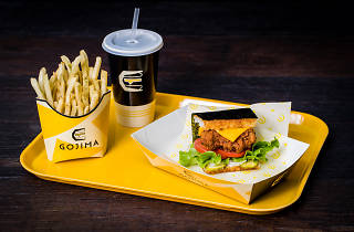 A rice burger, fries and a drink on a plastic tray