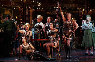 Women sit at a table drinking champaign in flapper-style lingerie on the set of La Boheme