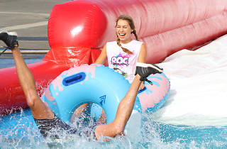 Woman and man sliding down a waterslide in the ROC Race Sydney