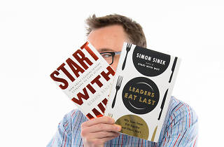 Simon Sinek holding his books 'Start with Why' and 'Leaders Eat Last'