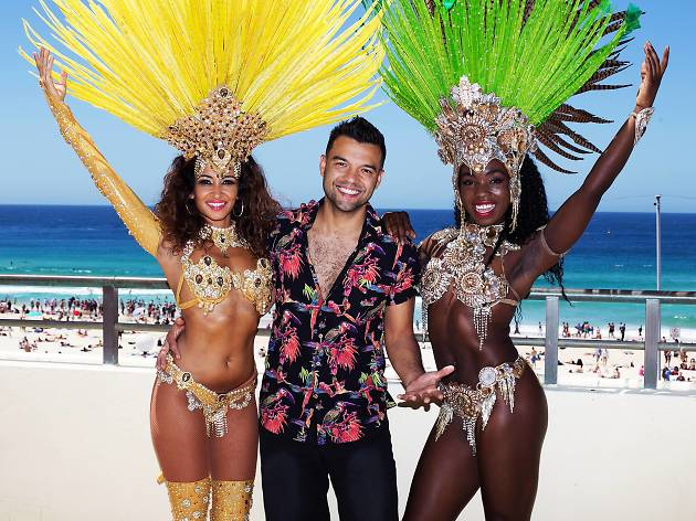 Man stands with dancers from Rhythm Brazil on either side