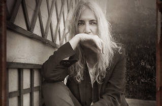 Patti Smith sits wearing a suit in a black and white portrait