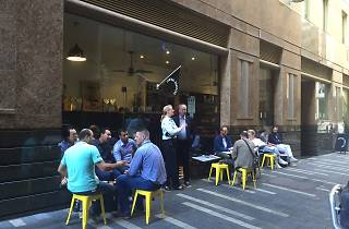 people sitting outside a cafe in a CBD laneway