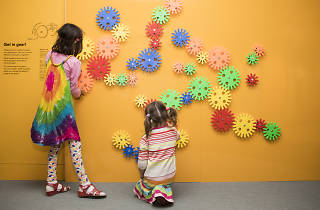 Girls playing with coloured cog shapes on wall