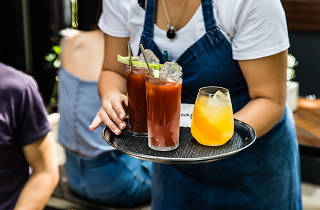 A waiter carries of tray of Bloody Mary and Mimosa cocktails during brunch at Surry Hills bar Dead Ringer