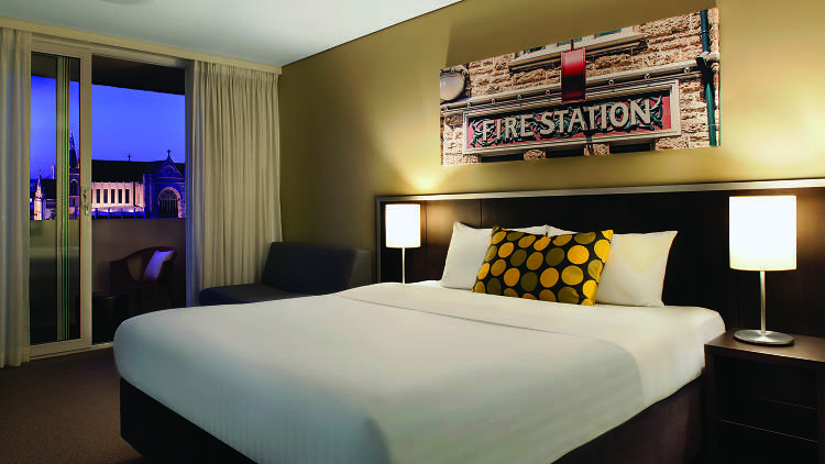 A guest room with balcony at the Travelodge Hotel Perth