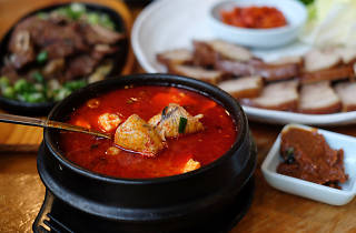 A bowl of red soup with tofu