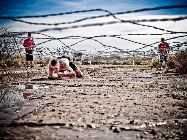 Man crawling under barbed wire