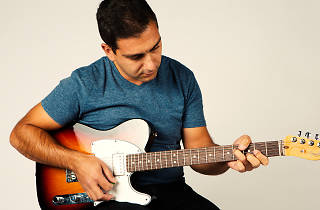 A man plays a Fender Telecaster electric guitar