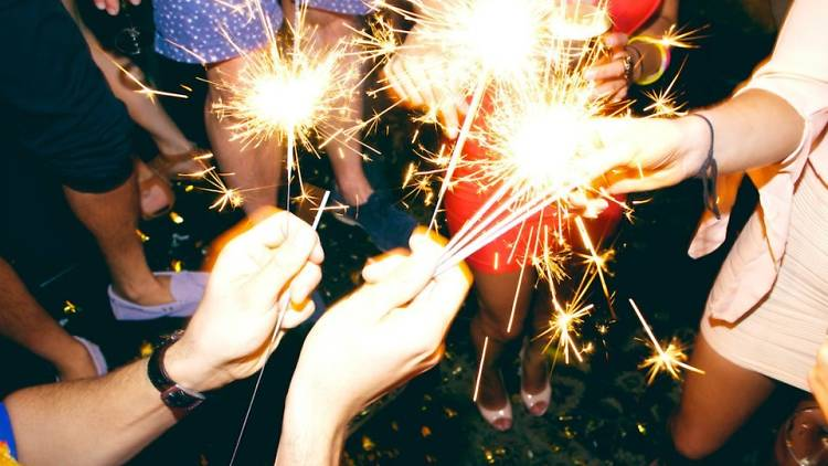 People lighting sparklers at a party