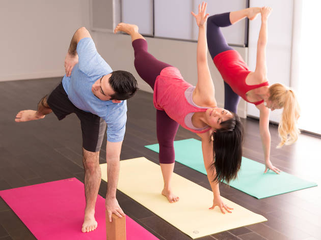 Three people performing yoga poses