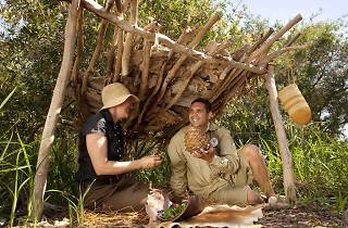 Woman and man sitting under natural shelter