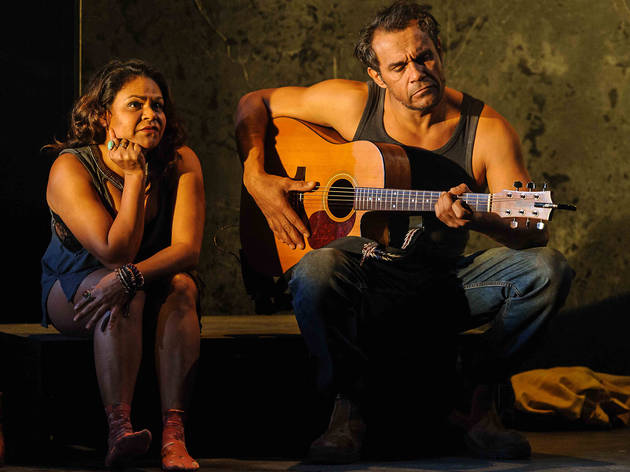 Production still of a scene in which actors Ursula Yovich and Aaron Pedersen sit side by side, as he plays the guitar