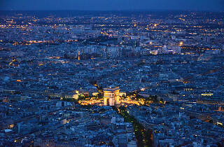 A view of the city at night, including the Arc de Triomphe