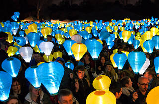 Blue, white and gold lanterns held by people at Light the Night