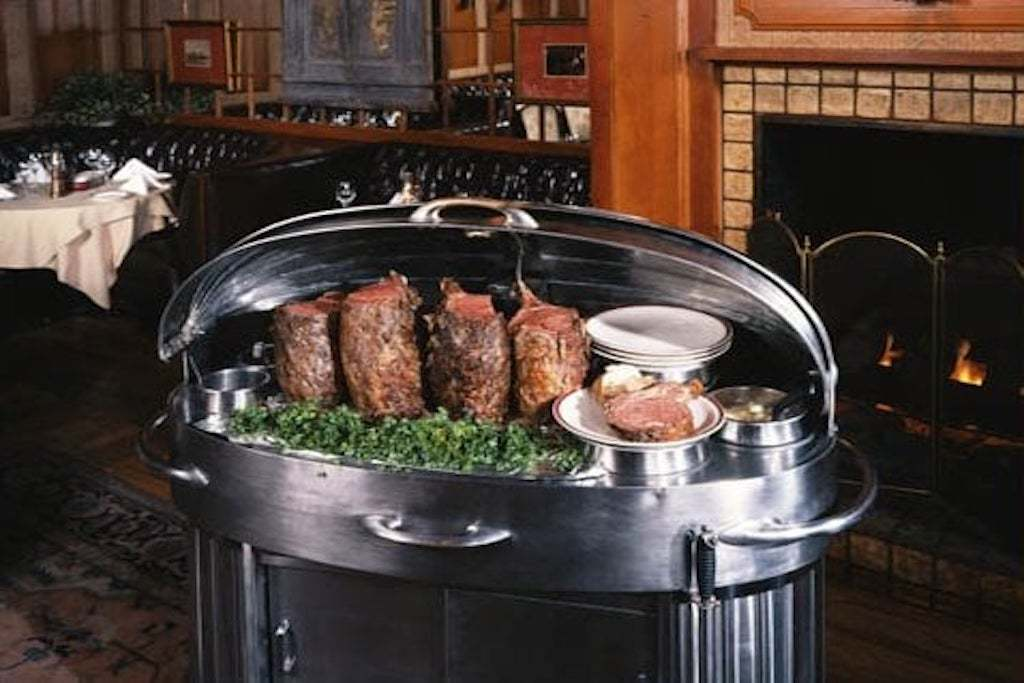 Prime rib inside stainless steel serving cart