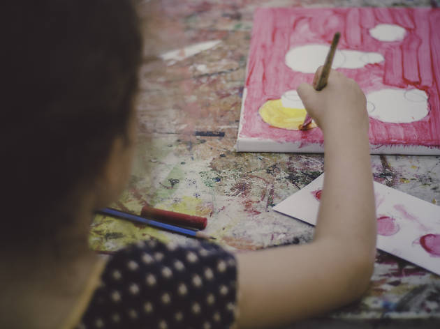 Child painting yellow and pink on canvas