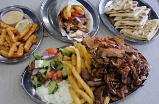 A mixed meat plate of meats, chips and salad