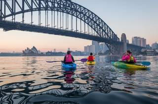Three people kayaking toward harbour bridge for Sydney by Kayak