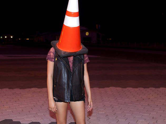 Playful young woman with a traffic cone on her head – Ha! As if that's the caption.