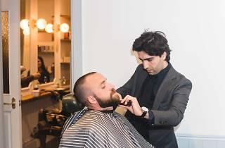 Man shaving another man