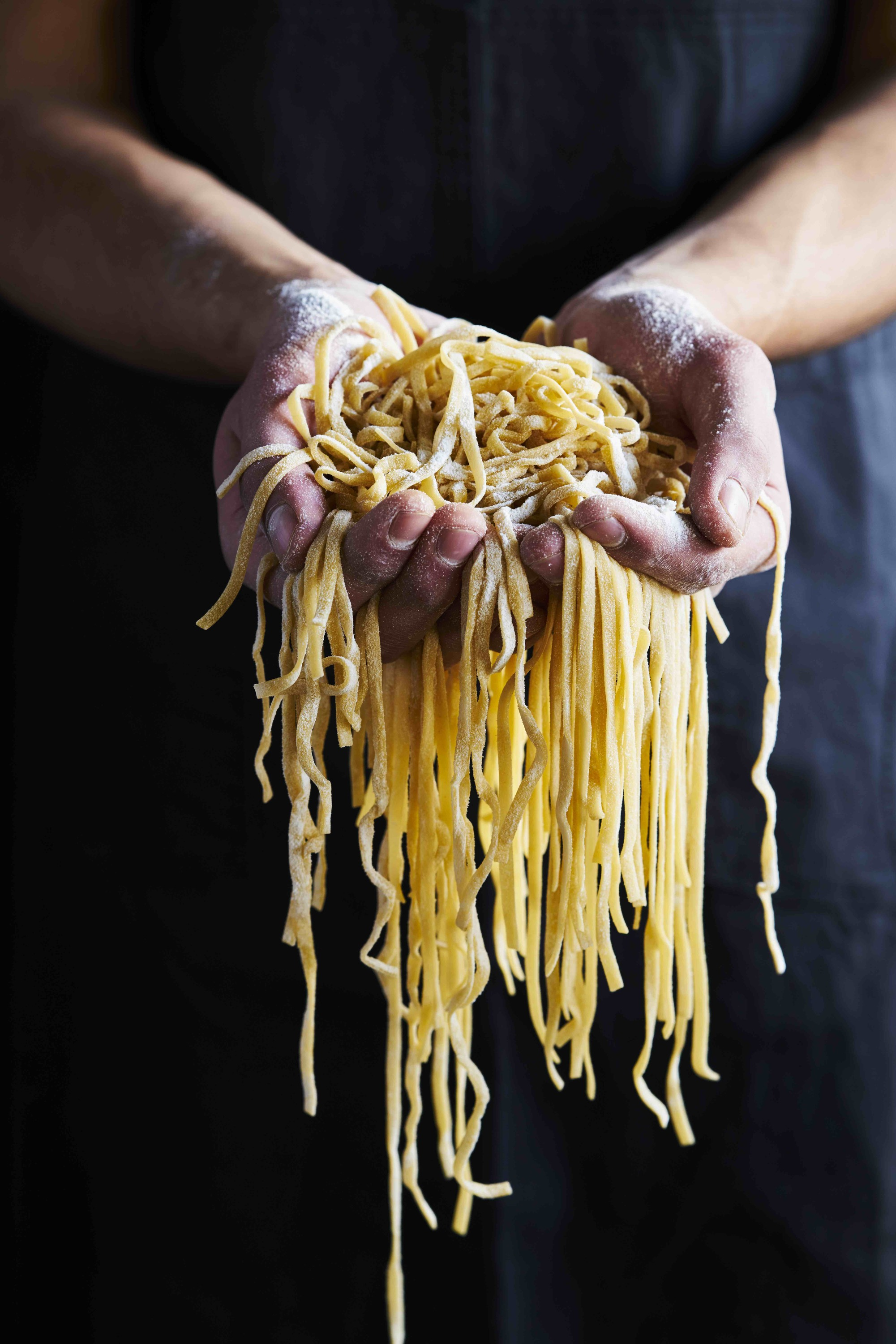 Hands holding fresh pasta