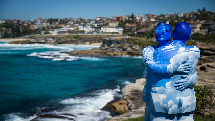 A sculpture of two people with their bodies painted like the sky embracing Sculpture by the Sea 2017