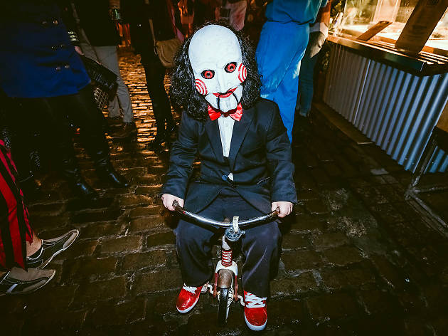 Person in a jigsaw costume on a bike