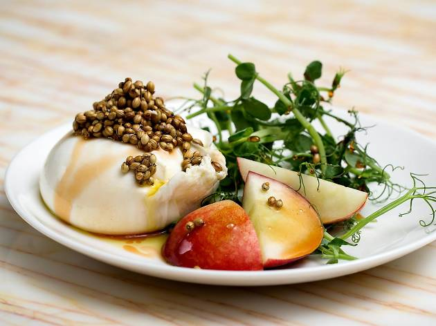 A plate of burrata and peach with coriander seeds at NOPI