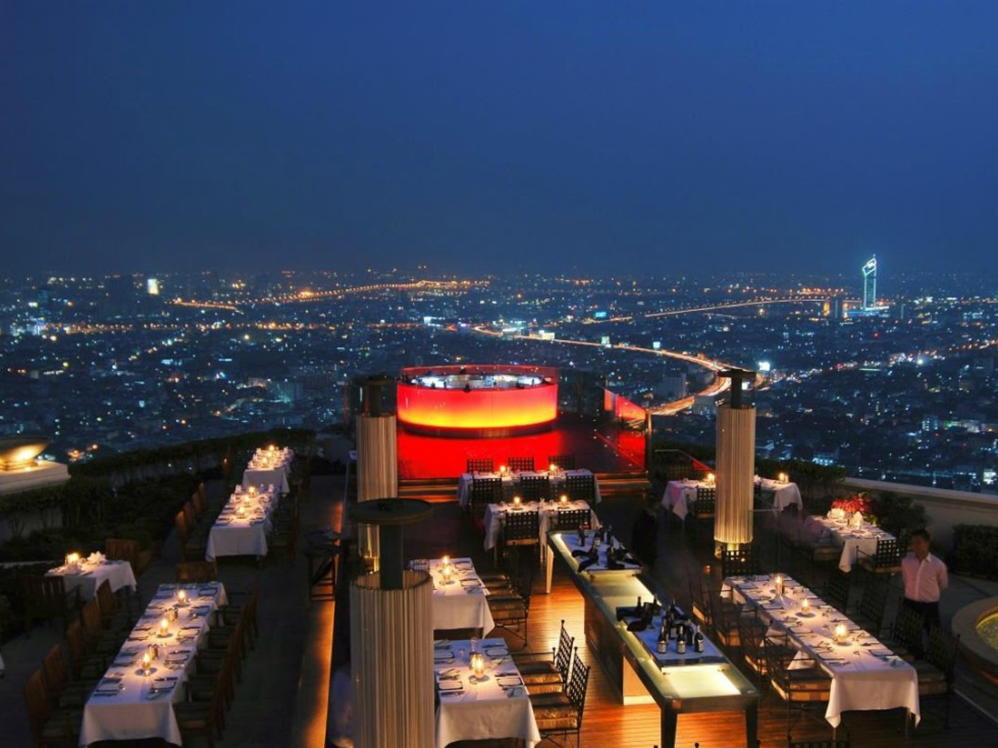 Rooftop cocktail bar overlooking the Bangkok night skyline