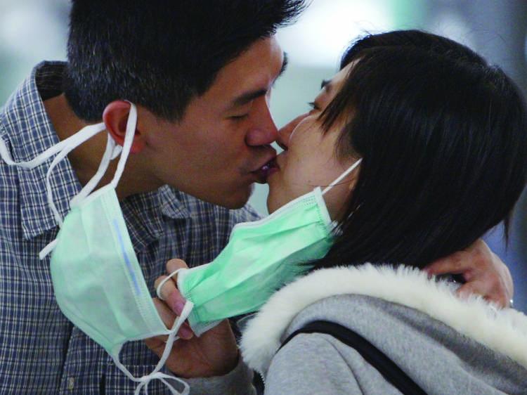 A couple remove their masks to say goodbye at Hong Kong airport
