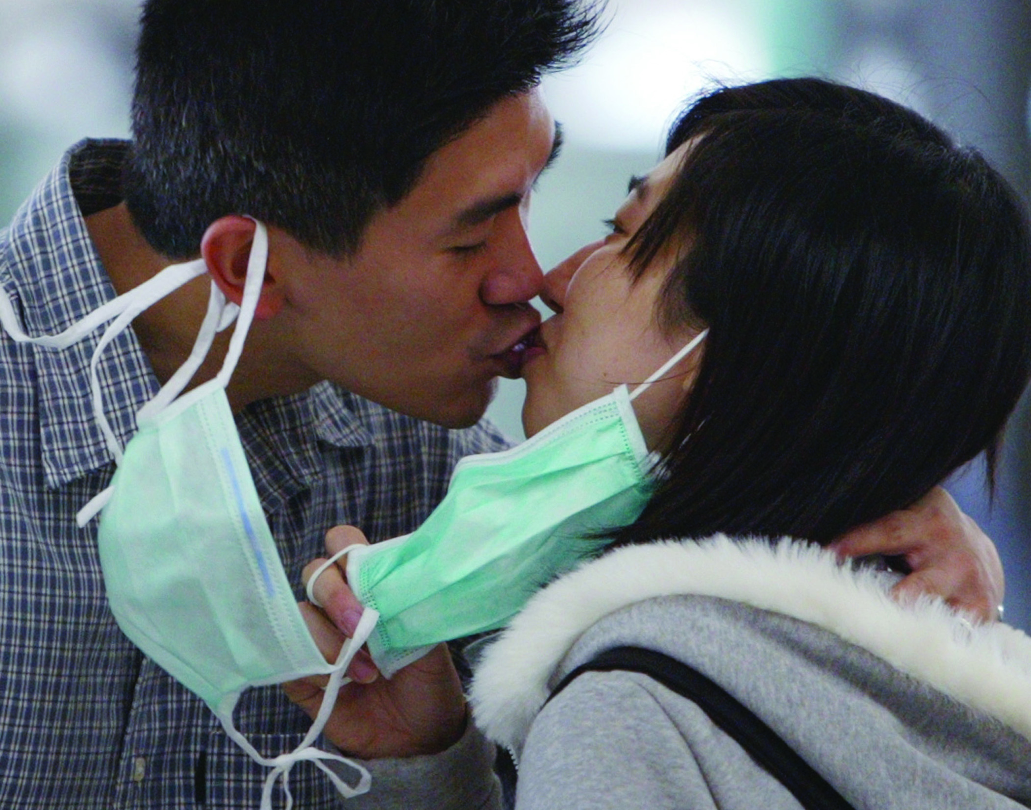 A couple remove their masks to say goodbye at Hong Kong airport