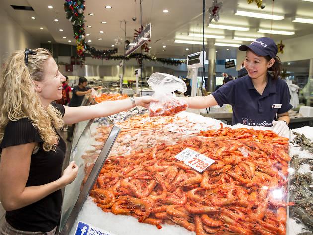 Woman buying prawns at the fish market