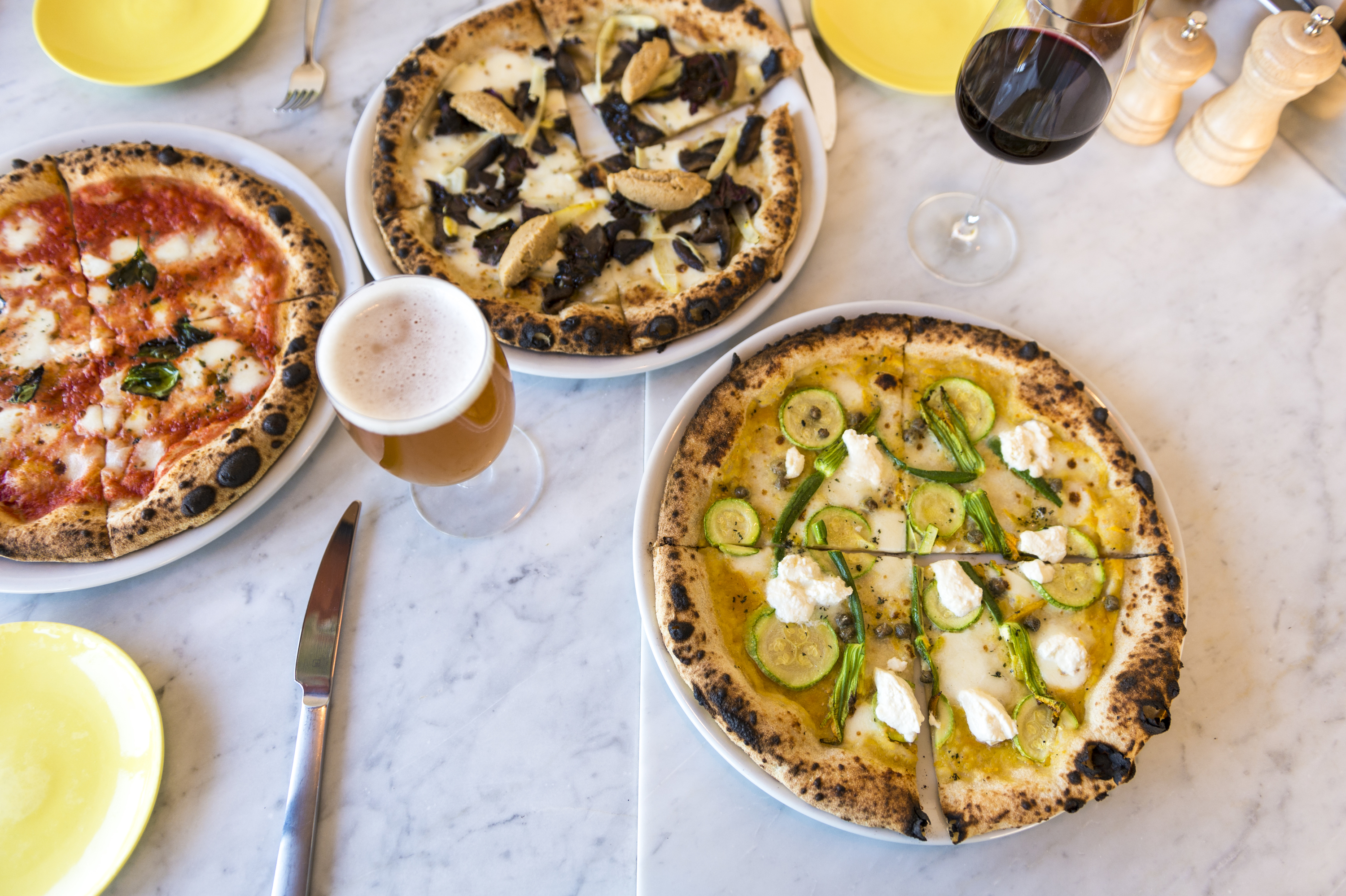 Three pizzas and drinks on a table