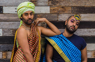 The 2 Boys in Saris pose in front of a wooden wall