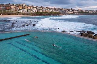 Man swimming with view of city at Bronte Pools Baths