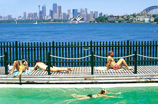 People swimming with a view of sydney harbour at MacCallum Pools