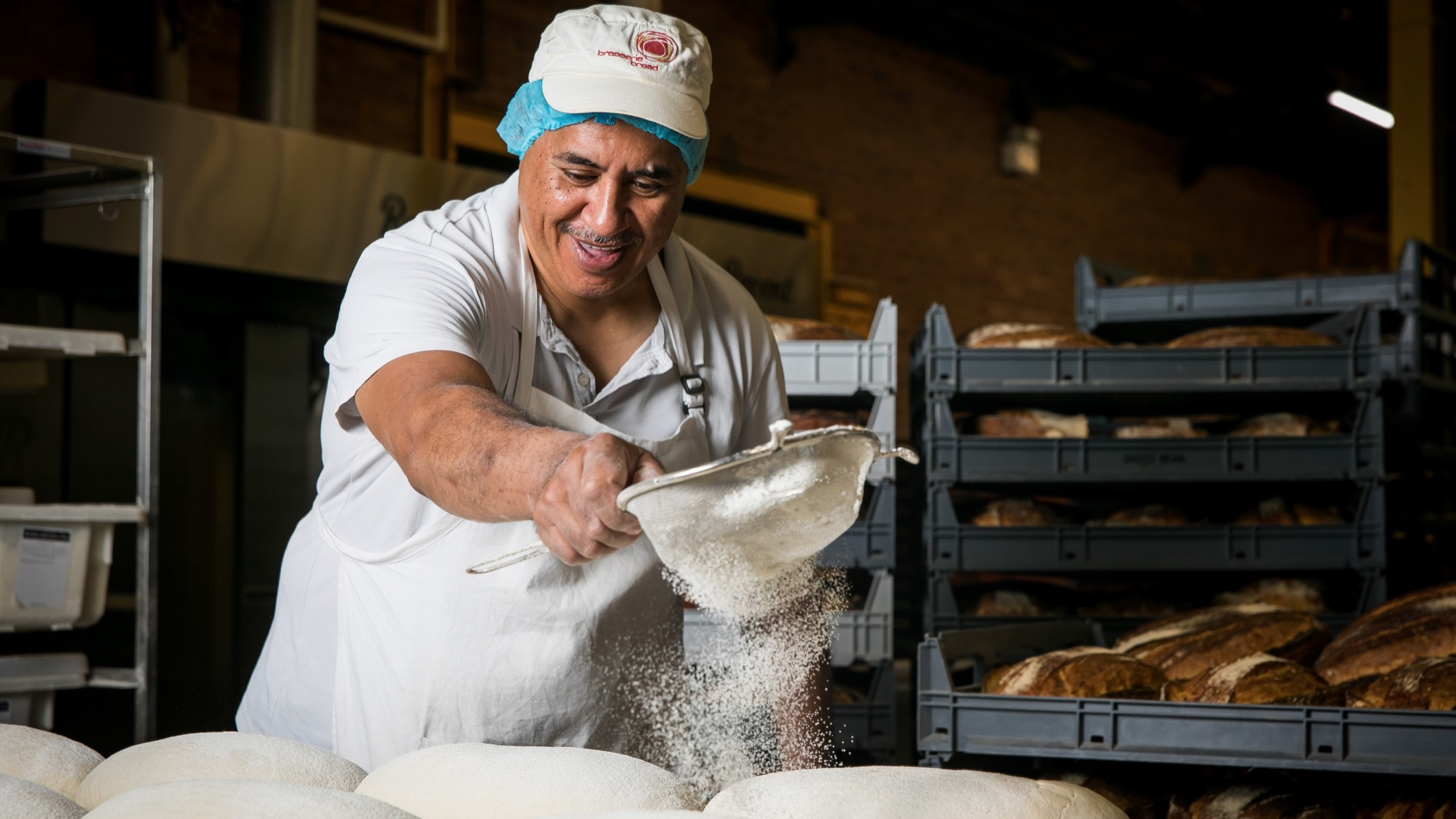 Baker shaking flour over dough at Brasserie Bread